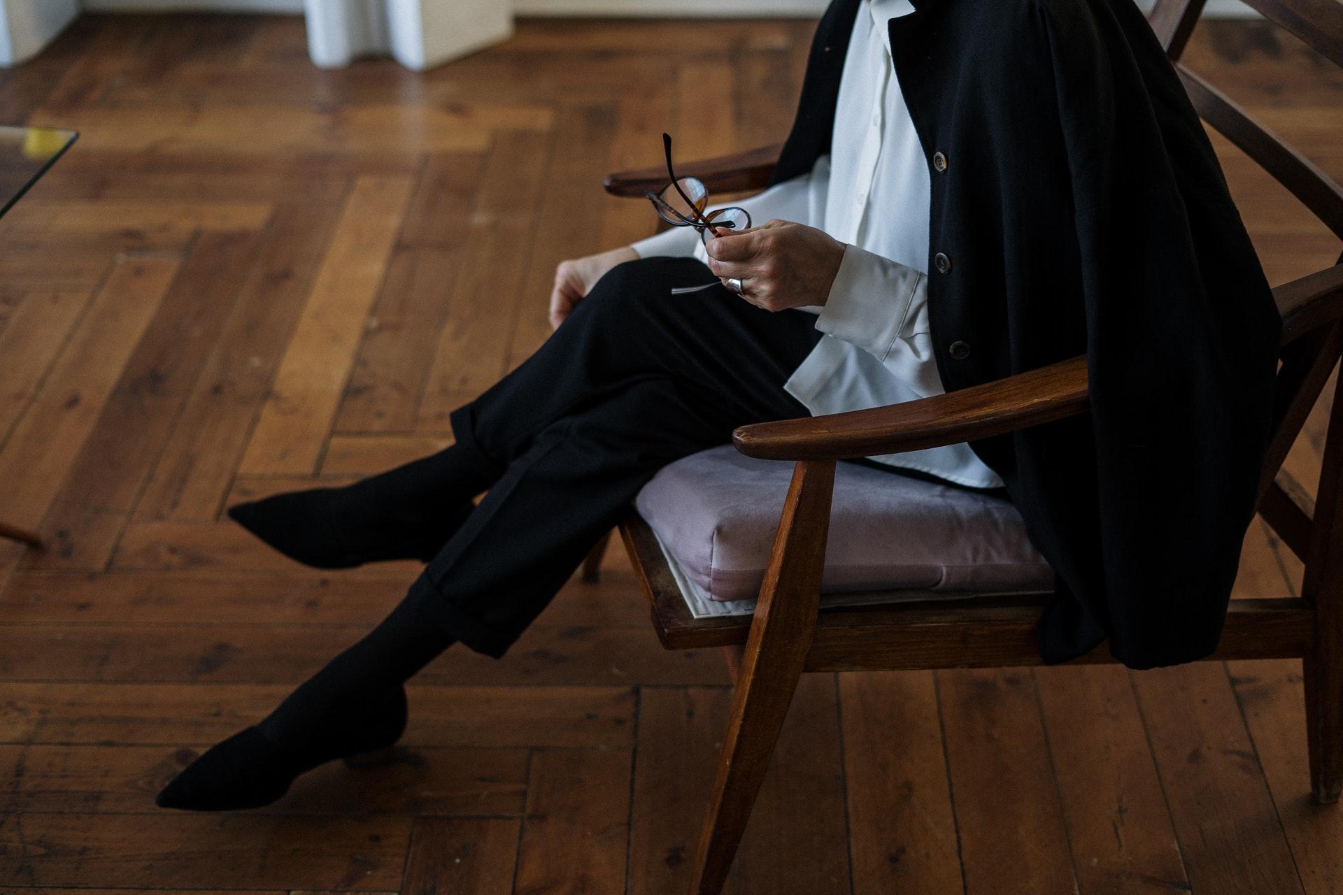 眼鏡をもって座る女性