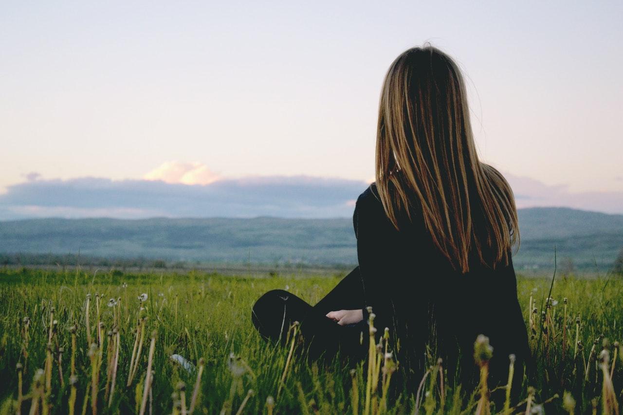 草原を見つめる女性