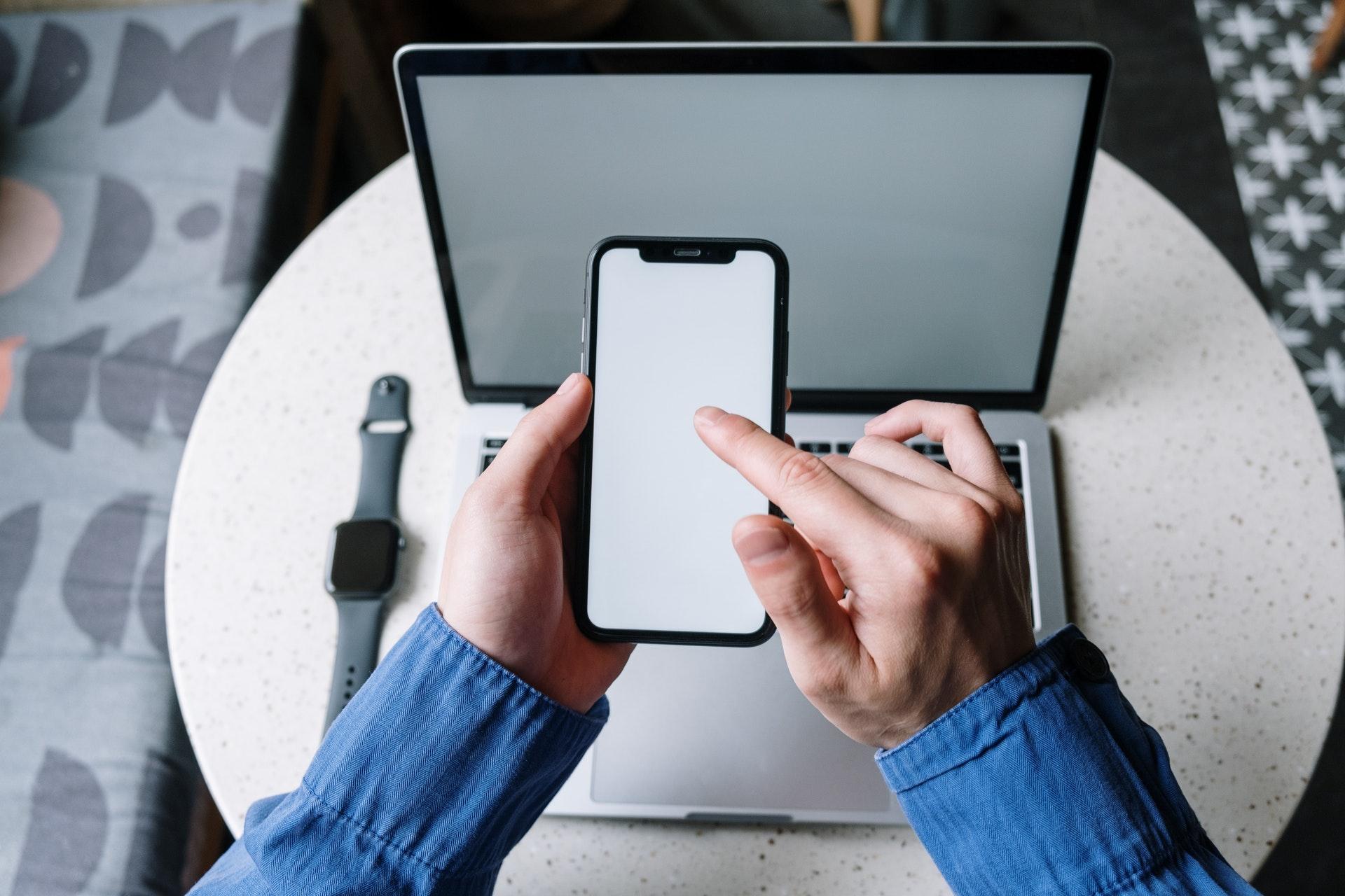 パソコンの合間にスマホを操作する男性の手