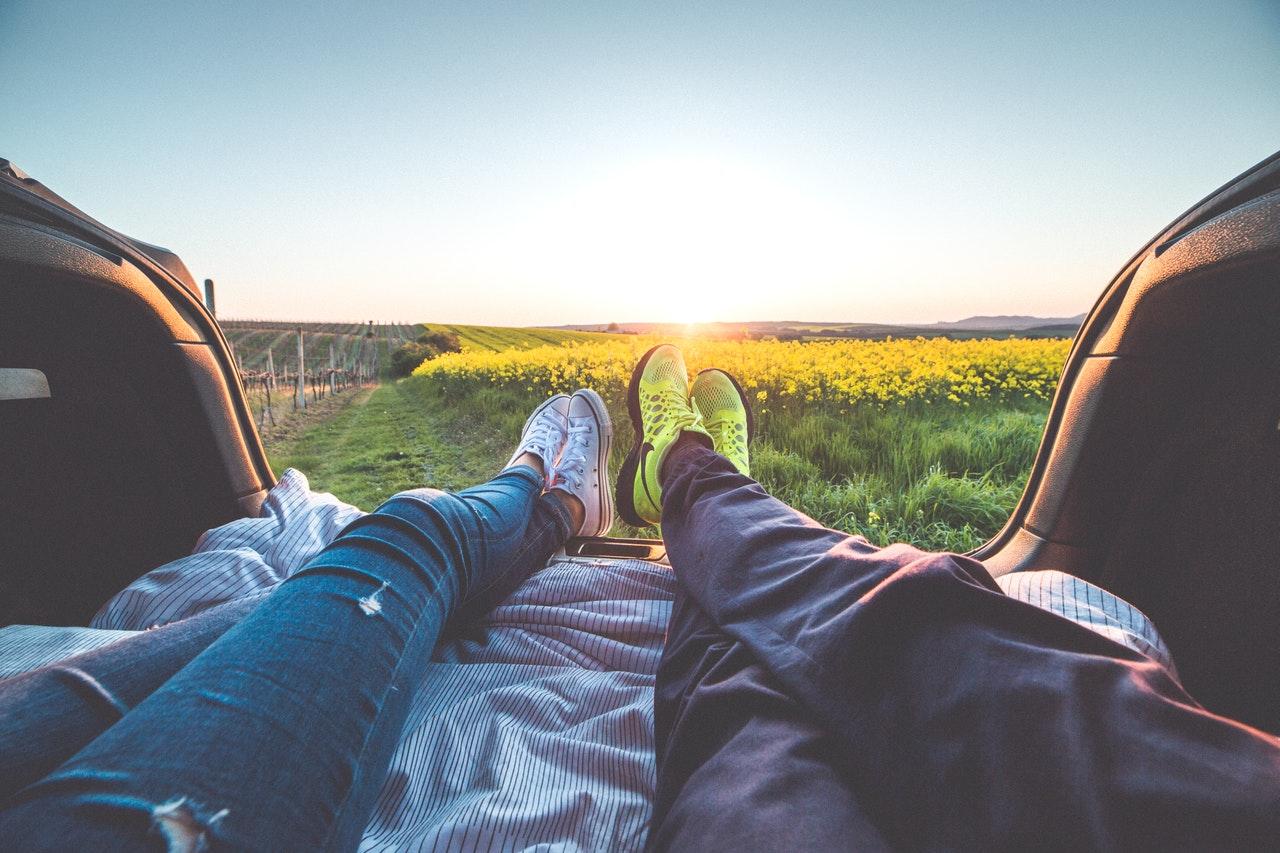 草原で寝転がるカップル