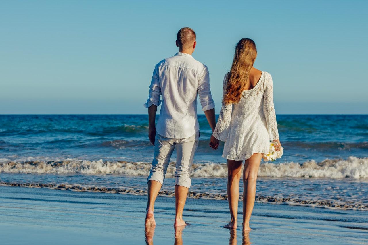 砂浜で手を繋ぐカップル