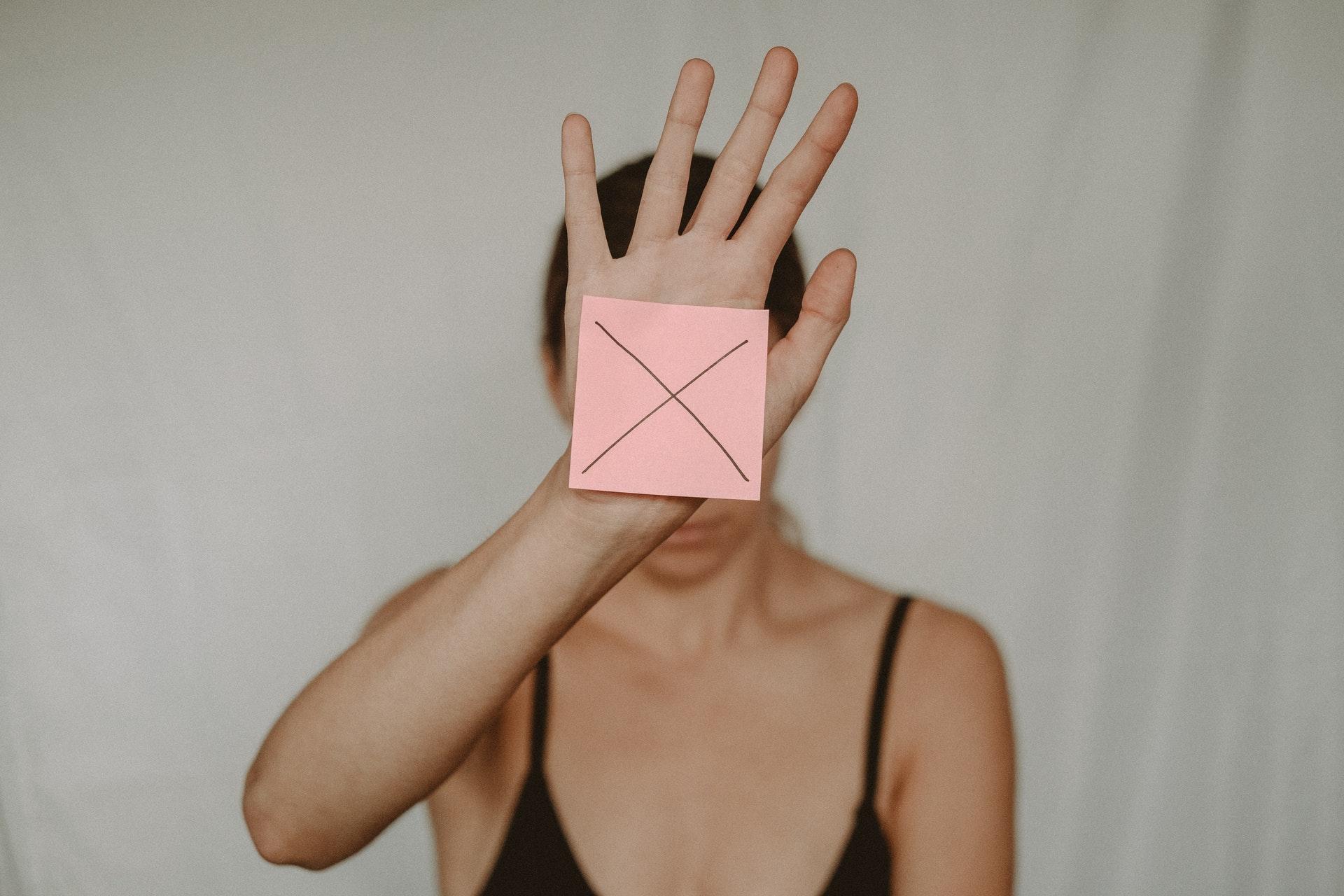 手にばつ印のメモを張っている女性