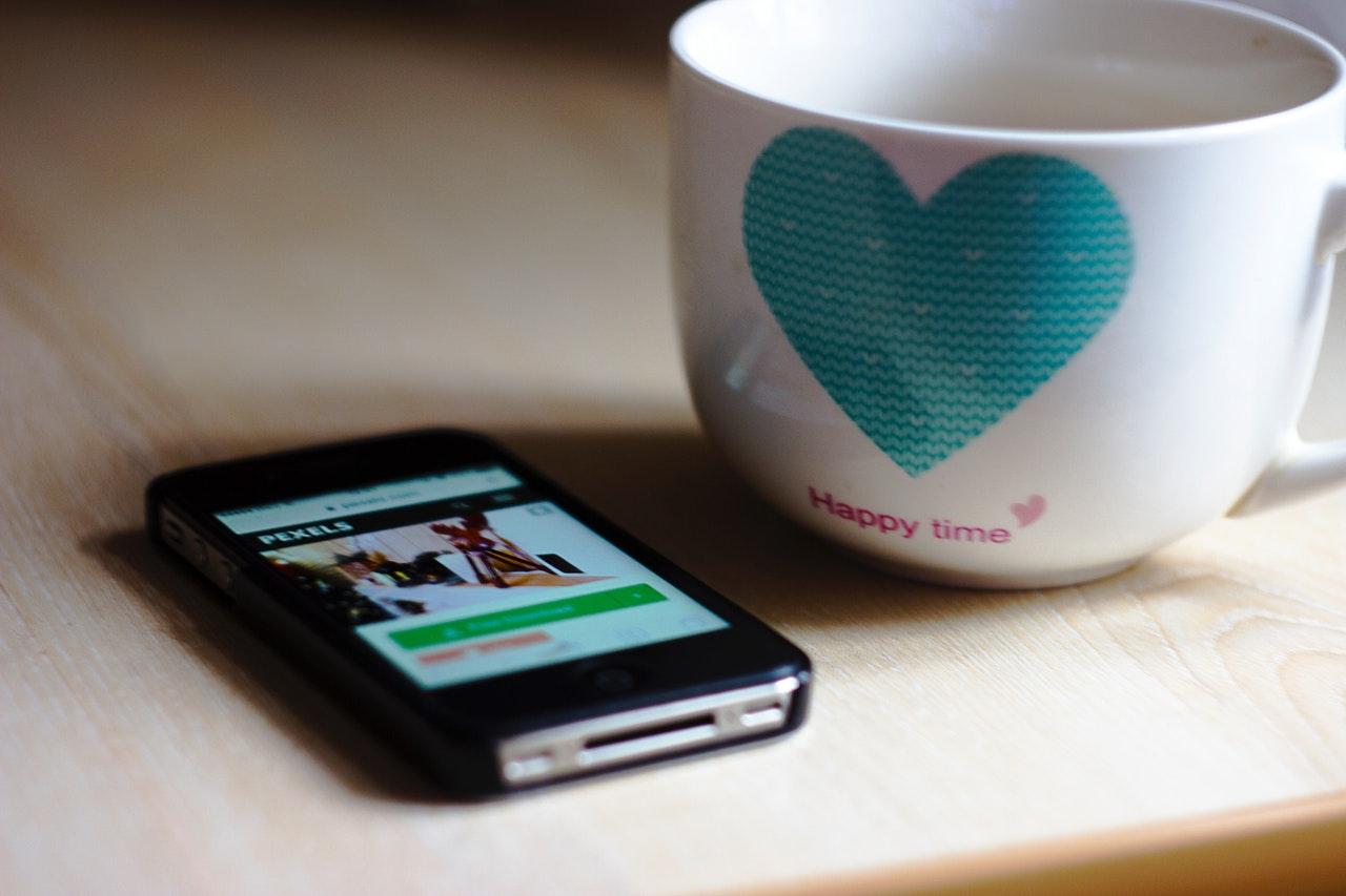 スマートフォンとハート柄のカップ
