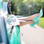 woman's legs outside a car in mint/teal