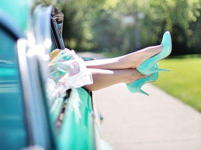 woman's legs outside a car in mint/teal