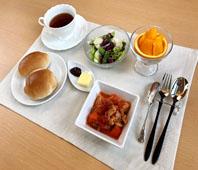朝の献立:パン、トマト煮、サラダ、果物、紅茶