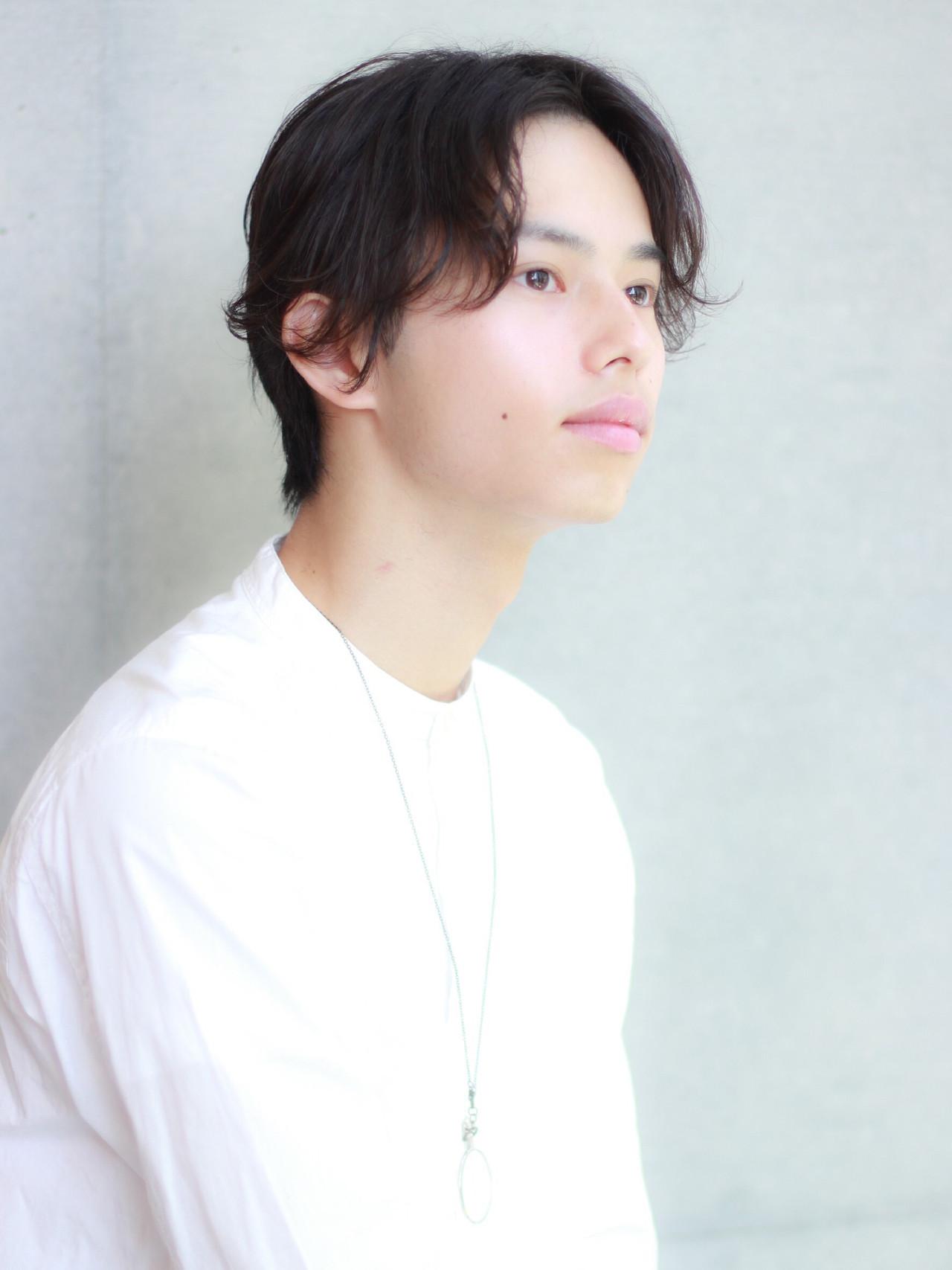 シンプルな白シャツにセンターパートヘアが似合うイケメン男性