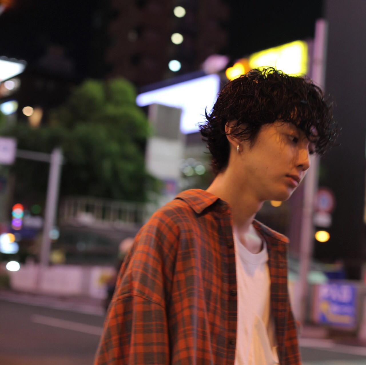 チェックシャツを羽織った黒髪パーマのイケメン男性