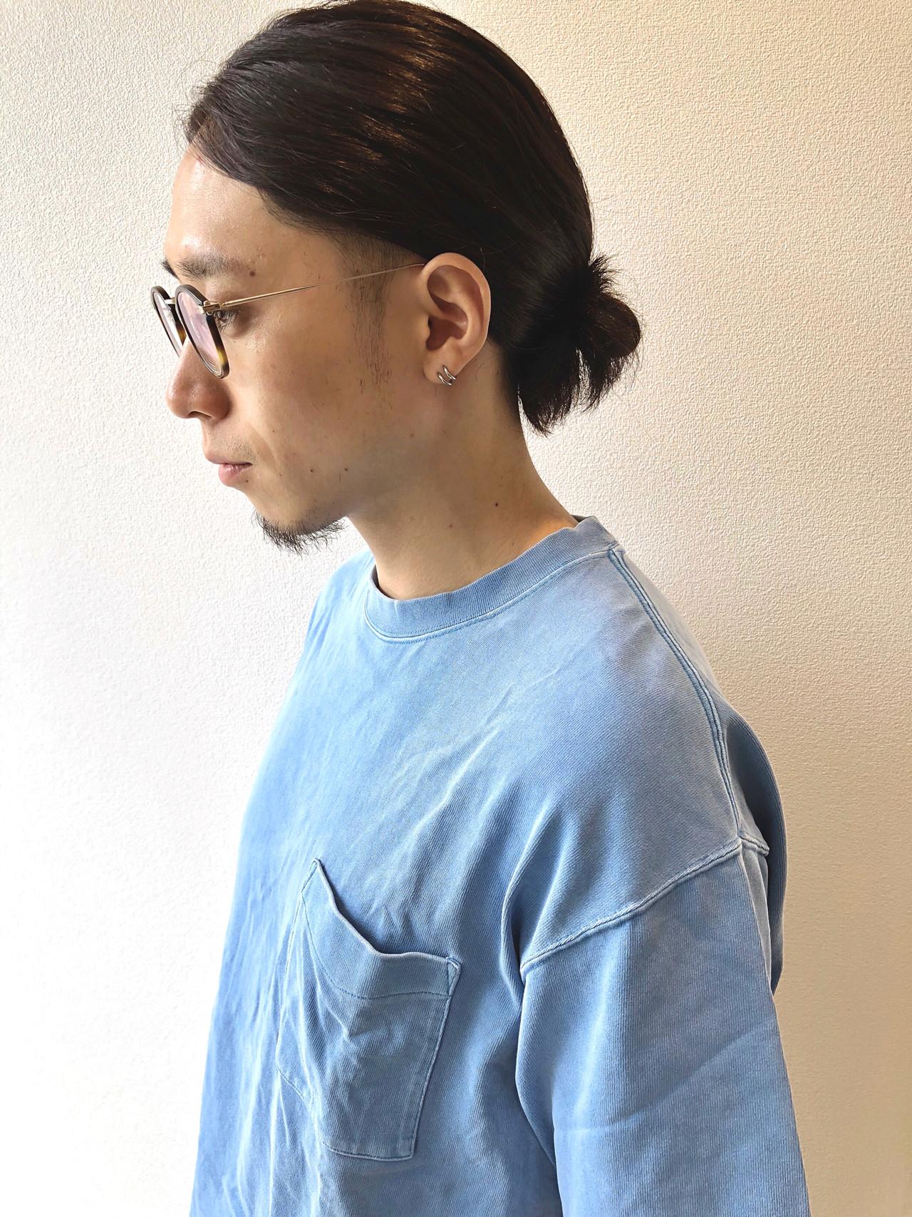 髪をひとつ結びにしたロングヘアの男性