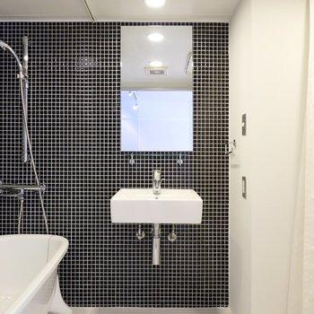 上品なネイビーのタイルに包まれた空間に入ると、正面にミニマルな洗面台がお出迎え。