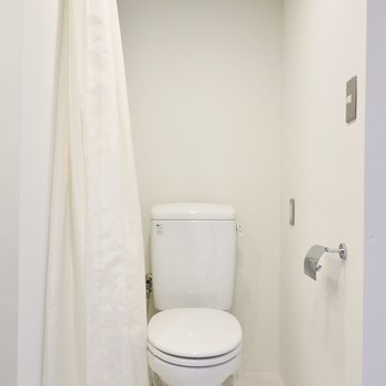 トイレも洗面台のお隣に。ネイビーのタイルとは対照的な真っ白な空間。