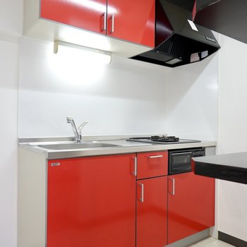 黒基調のLDKに合わせた真っ赤なキッチンです。