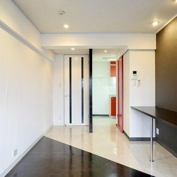 玄関の隣の奥まったスペースにはキッチン。その近くの赤い引き戸の先にはその他の水回りが。