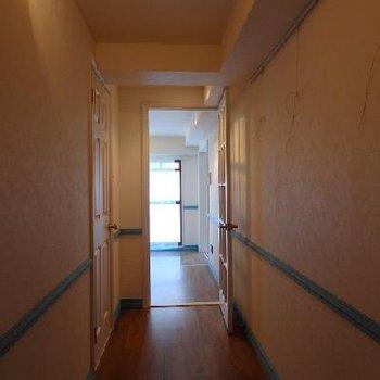 廊下にはブルーのライン。右手に映るのはピクチャーレール。絵など飾っておけますね