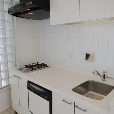 キッチンはガラスブロックの奥に。2口ガスコンロで食洗機も付いています(※写真は8階の反転間取り別部屋のものです)
