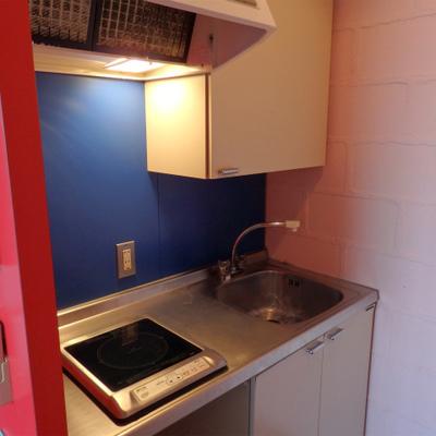コンパクトな1口IHキッチンの下には小型の冷蔵庫置きがありま ※写真は別部屋