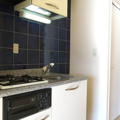 黒タイルが光るキッチンの前には収納棚つきです