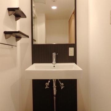 大きな鏡と飾り棚のある洗面台。