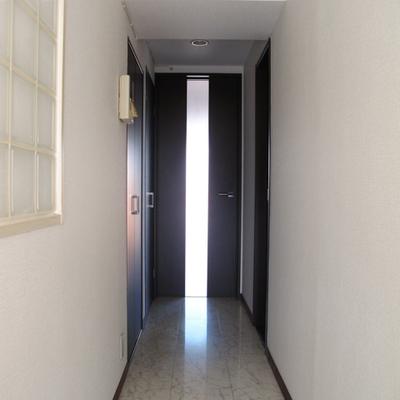 廊下左手に、収納と洗濯機置き場、右手にバストイレです。