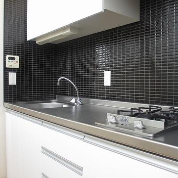 ブラックタイルのキッチンはオシャレさと利便性を兼ね備えています。 ※写真は別部屋です