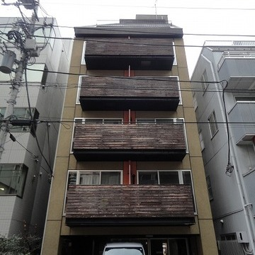 木のベランダが特徴的な縦長のマンションです