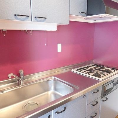 赤い壁紙がキャッチーなキッチン