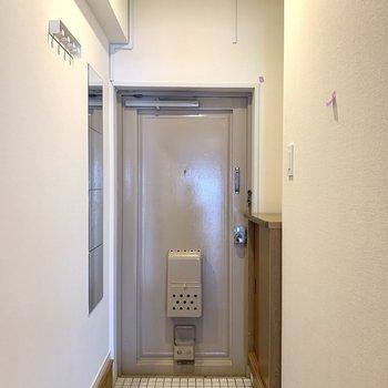 玄関は白タイルで明るく