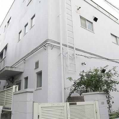 住宅地の一角にある白に塗装された3階建て