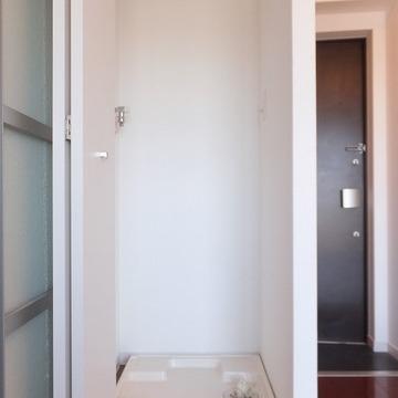 洗濯機置き場は扉付きで室内に。※写真は別部屋