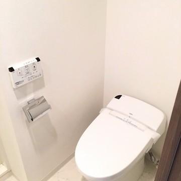 トイレは洗面台の向かい側に。上には扉付きの収納棚。