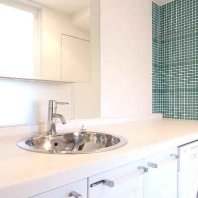 グリーンのタイルと洗面ボウルがかわいい。広さもピカイチ。ドラム式洗濯機はこの下に。