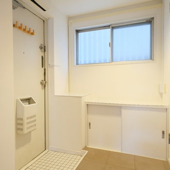 玄関の白いタイルと、モルタル調のPタイル