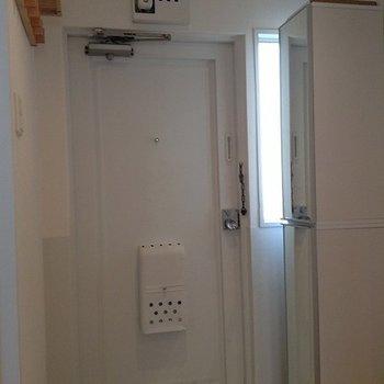 玄関扉も白。右に下駄箱あり