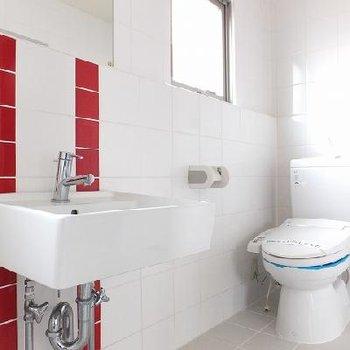 赤がアクセントの水回り。洗濯機はトイレの右側に置きます。