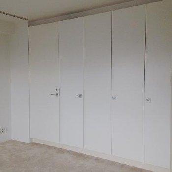 壁一面収納。左手からトイレ・お風呂へ ※写真は別部屋