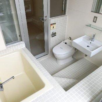 ライトグレーのタイル張りバスルーム。