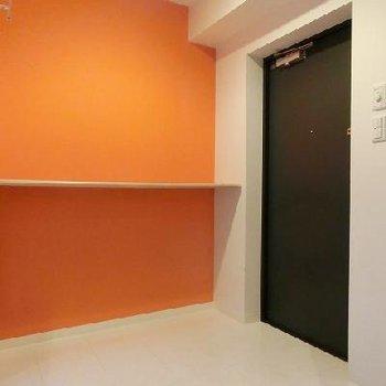 ポップなオレンジの壁紙がポイントの玄関横