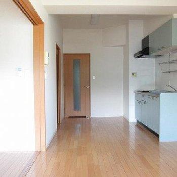 パステルカラーのキッチンとフローリングが明るい室内を演出