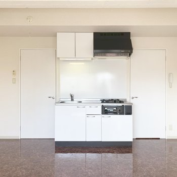 キッチン側。3口ガスのシステムキッチン。左のドアが廊下と玄関、右が水回り。