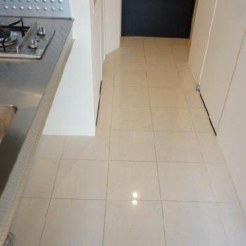 玄関〜キッチンの床はひとつづきのタイル。※写真は別部屋