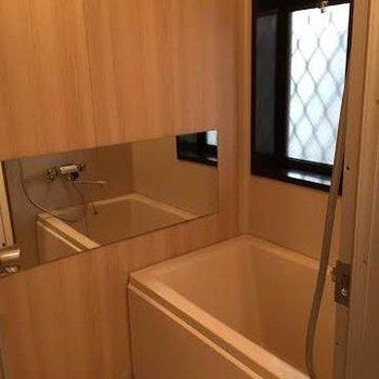 木目調のシートと大きな鏡で清潔感のあるお風呂に