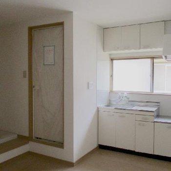 キッチンのお隣に浴室ドア(現在は取り替え済みの紙が貼られています)。