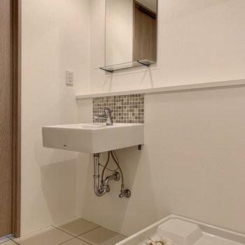 モザイクタイルがオシャレな洗面台と洗濯機置き場は隣り合っています。