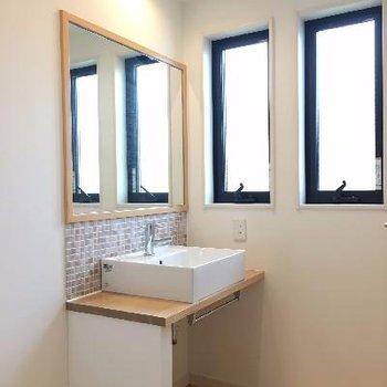 ワンステップ上がったところにタイル張りの洗面スペースがあります