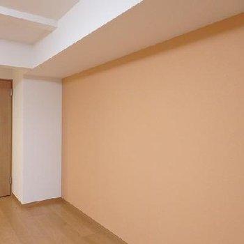オレンジとレンガ色の間のような色合いのクロス。※写真はどう間取りの別室