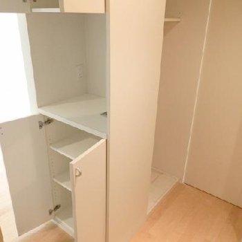 キッチンの収納。奥に見えるのは洗濯機置き場。※写真は別部屋です。