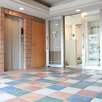 エントランスは可愛らしい色合いの床