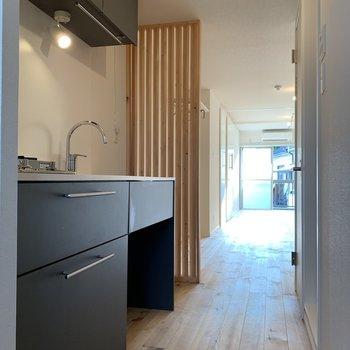 ネイビーのキッチンが無垢のナチュラル空間を引き締める