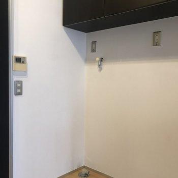 キッチンの隣に洗濯機置場がありました。上の棚には洗濯用品を収納すると良さそう。