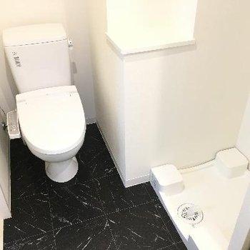 トイレと洗濯機置き場。黒の床がシックで格好良い。